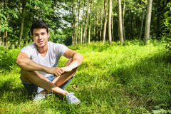 Fit handsome young man relaxing lying on lawn Stock Photos