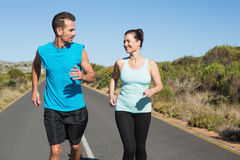 Fit happy couple jogging on the open road together Stock Photo
