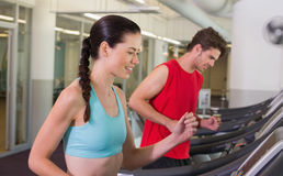 Fit happy couple running together on treadmills Stock Photography