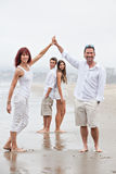 Fit happy Family at the beach. Mother and father holding arms up with their teenagers framed between them Stock Image
