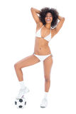 Fit happy girl in white bikini holding football at her foot Royalty Free Stock Images