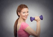 Fit happy girl working out. Lifting dumbbell isolated on grey wall background. Healthy life style concept stock photo