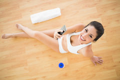 Fit happy woman sending a text during her workout looking at camera Stock Image