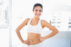 Fit happy woman in sportswear with hands on hips Stock Images