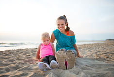 Fit, happy young mother and daughter in workout gear on beach Stock Photo