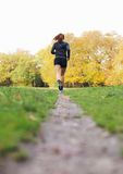 Fit and healthy female athlete running in park stock image