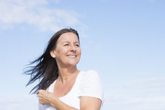 Fit healthy happy mature retired woman outdoor. Portrait attractive mature woman joyful and happy retired, keeping healthy and fit, isolated on blue sky Stock Photo