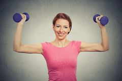 Fit healthy model woman flexing muscles lifting dumbbells Royalty Free Stock Images