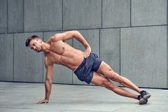 Fit healthy muscular young man with a bare chest doing side planks. In an urban environment royalty free stock photo