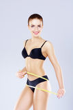 Fit, healthy and sporty woman in black swimsuit over grey background. Stock Photo