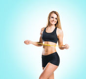 Fit, healthy and sporty woman in sportswear measuring her body i Royalty Free Stock Photos