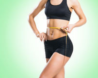 Fit, healthy and sporty woman in sportswear measuring her body i Stock Photo