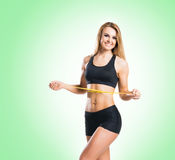 Fit, healthy and sporty woman in sportswear measuring her body i Stock Photos
