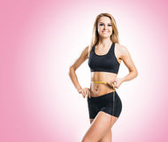 Fit, healthy and sporty woman in sportswear measuring her body i Stock Photography