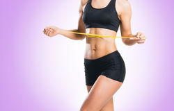 Fit, healthy and sporty woman in sportswear measuring her body i Royalty Free Stock Image