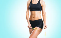 Fit, healthy and sporty woman in sportswear measuring her body i Stock Images
