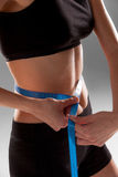 Fit and healthy waist measured with a tape Royalty Free Stock Photography