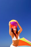Fit and healthy woman catching beach ball on sunny beach in Spain.
