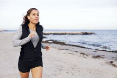 Fit and healthy woman jogging on beach. Beautiful young female model running outdoors. Caucasian female training on the beach with copyspcae royalty free stock images