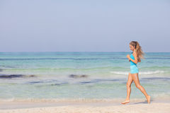 Fit healthy woman jogging or running on seashore Stock Photography