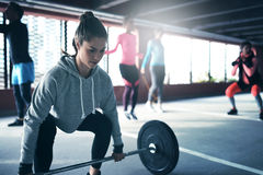 Fit healthy woman lifting a weight barbell. Fit healthy women lifting a weight barbell from floor, exercising with group of people outside urban setting Royalty Free Stock Photography