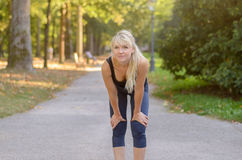 Fit healthy woman taking a break from jogging Stock Photography