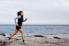 Fit and healthy young woman running along shoreline Royalty Free Stock Images