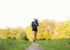 Fit and helathy young woman running in park stock photo