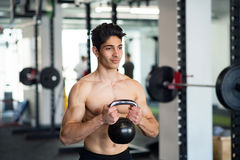 Young fit hispanic man in gym exercising with kettlebell. Royalty Free Stock Images