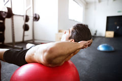 Fit hispanic man in gym training, working abs, doing crunches Royalty Free Stock Photos