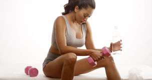 Fit Hispanic woman resting after lifting weights Stock Images