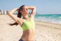 Fit hispanic woman stretches on the beach after a run Royalty Free Stock Image
