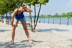 Fit jogger woman resting after run in city park. Royalty Free Stock Image