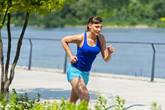 Fit jogger woman resting after run in city park. Stock Photos