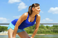 Fit jogger woman resting after run in city park by the river. Stock Photography