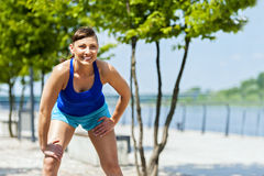 Fit jogger woman resting after run in city park. Stock Image