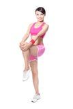 Fit kvinnaholding henne ben som ska värmas upp Arkivbild