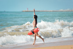 Fit lady in bikini with life-saver running into Stock Photos