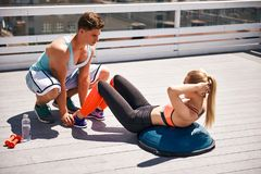 Male coach is supervising woman exercising with outfit royalty free stock image
