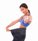 Fit lady happily pulling jeans on waist Royalty Free Stock Image