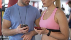 Fit lady showing application tracking her results to personal trainer in gym. Stock footage stock footage