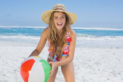 Fit laughing blonde in white bikini and straw hat holding beach ball Royalty Free Stock Image