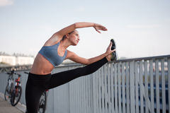Fit lean blond beauty. Fit lean blond beauty exercising outdoors in the city Royalty Free Stock Photos