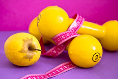 Fit life: dumbbells, measuring tape and apple Royalty Free Stock Photography