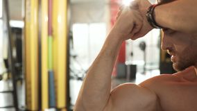 Fit male admiring his developed muscles, doing front double bicep pose in gym. Stock footage stock video