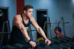 Fit male athlete getting ready for dumbbell workout. Handsome man at fitness gym take rest and breathe. Fitness, bodycare and active lifestyle concept Royalty Free Stock Images