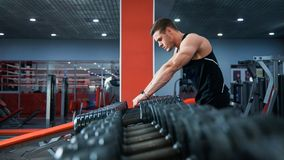 Fit male athlete getting ready for dumbbell workout. Handsome man at fitness gym take rest and breathe. Fitness, bodycare and active lifestyle concept Stock Image