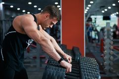 Fit male athlete getting ready for dumbbell workout. Handsome man at fitness gym take rest and breathe. Fitness, bodycare and active lifestyle concept Royalty Free Stock Photography