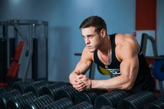 Fit male athlete getting ready for dumbbell workout. Handsome man at fitness gym take rest and breathe. Fitness, bodycare and active lifestyle concept Stock Photography