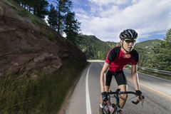 Fit male bicyclist wearing red jersey riding mountain road. Stock Photo